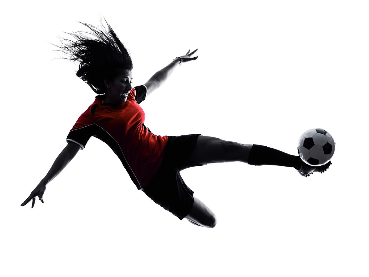 Woman in Air Kicking Soccer Ball